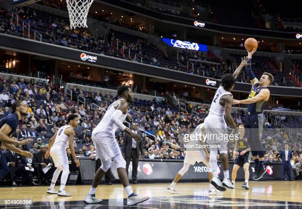 Marquette Golden Eagles guard Andrew Rowsey goes for a long shot over Georgetown Hoyas guard Jonathan Mulmore during a Big East men's basketball game...