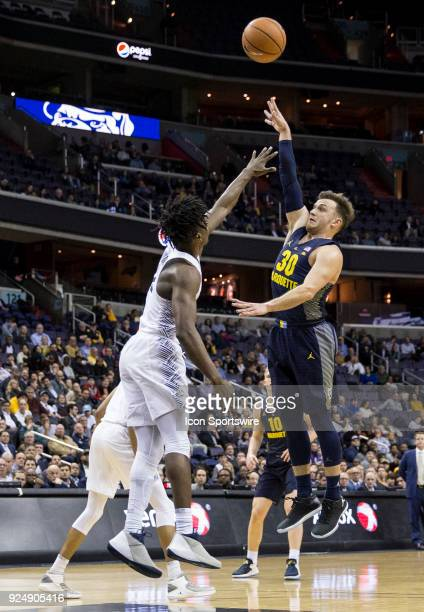Marquette Golden Eagles guard Andrew Rowsey launches a shot over Georgetown Hoyas guard Jonathan Mulmore during a Big East men's basketball game...