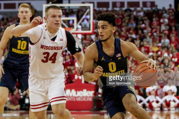 Marquette Golden Eagles guard Markus Howard drives past Wisconsin Badger guard Brad Davison during an college basketball game between Marquette...