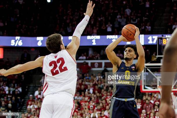 Marquette Golden Eagles guard Markus Howard take a step back 3 pointer over Wisconsin Badger forward Ethan Happ as time expires during an college...