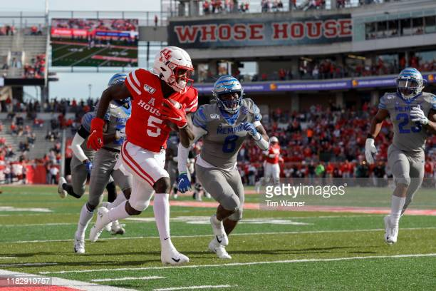 Marquez Stevenson of the Houston Cougars catches a pass and runs for a touchdown defended by Xavier Cullens of the Memphis Tigers in the first...