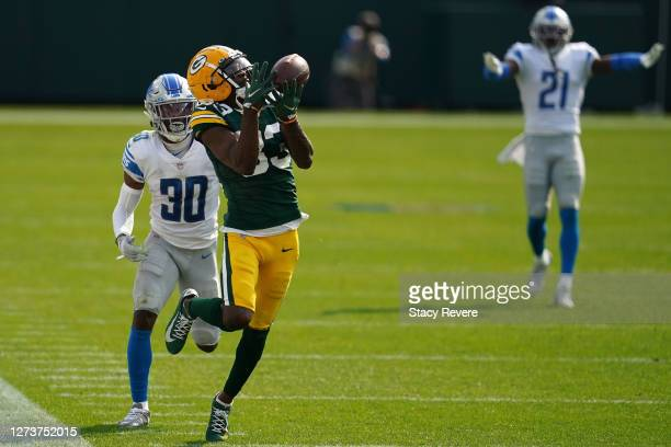 Marquez Valdes-Scantling of the Green Bay Packers catches a pass in front of Jeff Okudah of the Detroit Lions during the second half at Lambeau Field...
