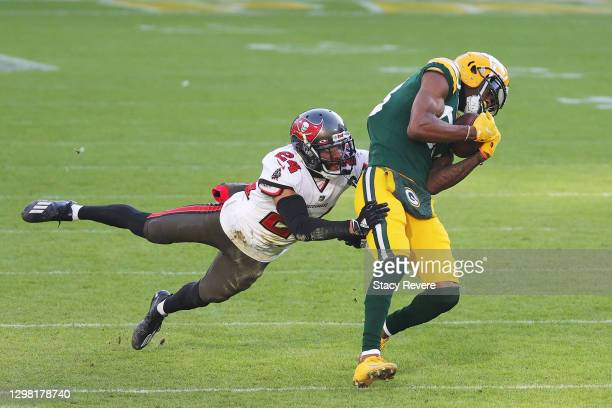 Marquez Valdes-Scantling of the Green Bay Packers completes a touchdown reception against the defense of Carlton Davis of the Tampa Bay Buccaneers in...