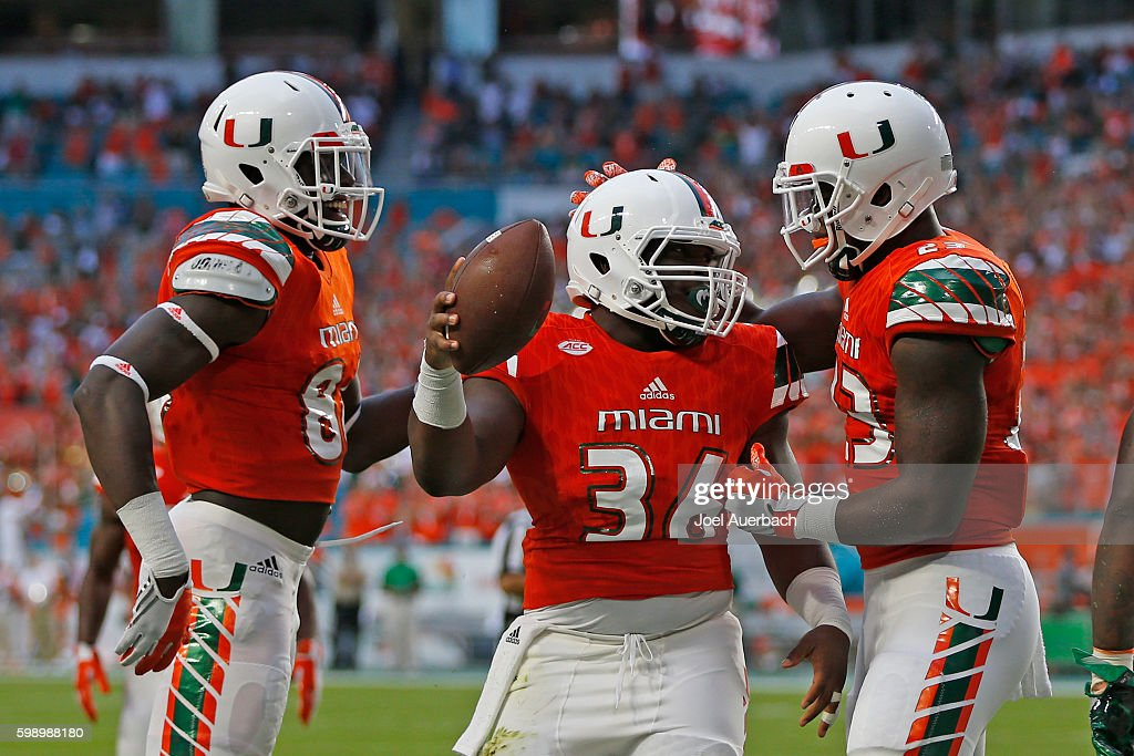 Marquez Williams #36 is congratulated by Christopher Herndon IV #23 and David Njoku #86 of the Miami Hurricanes after scoring a touchdown against the Florida A&M Rattlers on September 3, 2016 at Hard Rock Stadium in Miami Gardens, Florida.