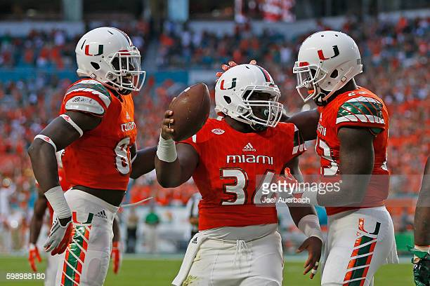 Marquez Williams is congratulated by Christopher Herndon IV and David Njoku of the Miami Hurricanes after scoring a touchdown against the Florida AM...