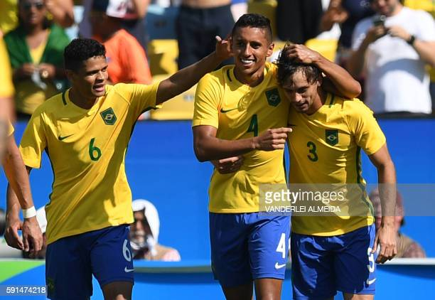 Marquinhos of Brazil celebrates with teammates Rodrigo Caio and Douglas Santos after scoring the 4th goal against Honduras during their Rio 2016...