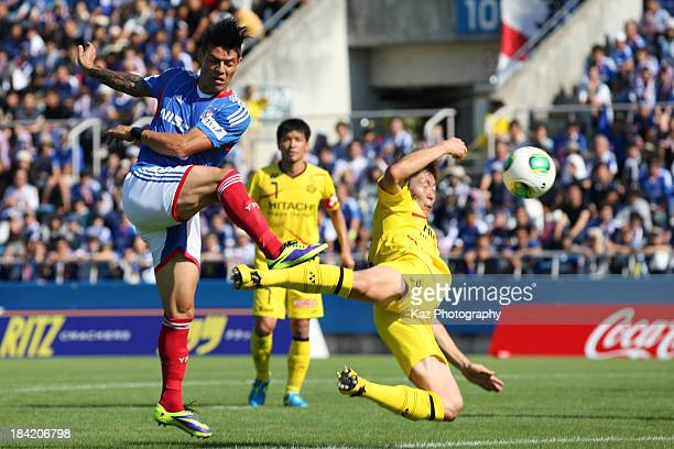 Marquinhos of Yokohama F.Marinos scores his team's first goal past the tackle by Naoya Kondo of Kashiwa Reysol during the Yamazaki Nabisco Cup semi...