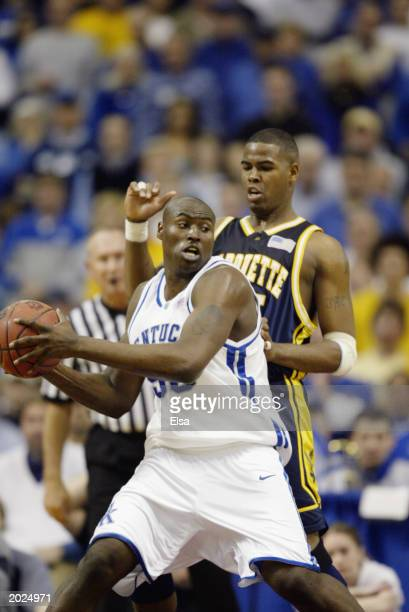 Marquis Estill of the University of Kentucky Wildcats is defended by Robert Jackson of the Marquette University Golden Eagles during the Midwest...