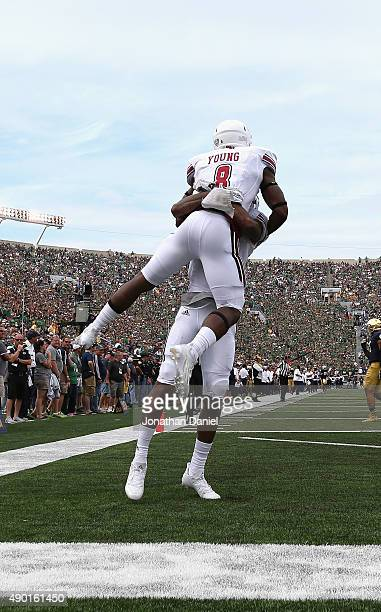 Marquis Young of the Massachusetts Minutemen is lifted by teammate Tajae Sharpe after scoring a touchdown against the Notre Dame Fighting Irish at...