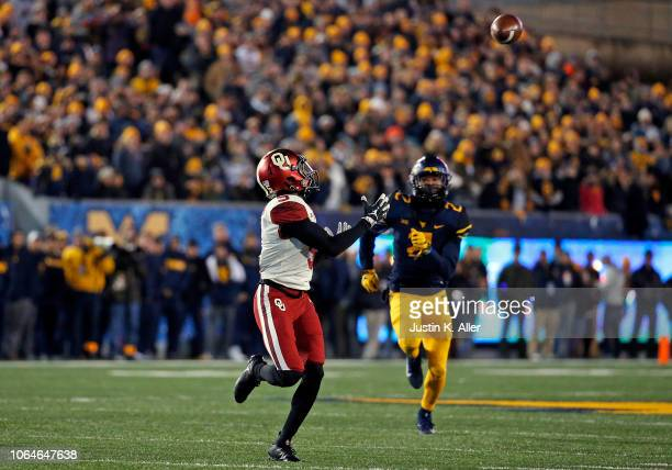 Marquise Brown of the Oklahoma Sooners catches a 65 yard pass against the West Virginia Mountaineers on November 23 2018 at Mountaineer Field in...