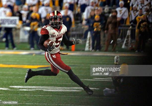 Marquise Brown of the Oklahoma Sooners catches and runs for a 45 yard touchdown against Toyous Avery Jr #3 of the West Virginia Mountaineers on...
