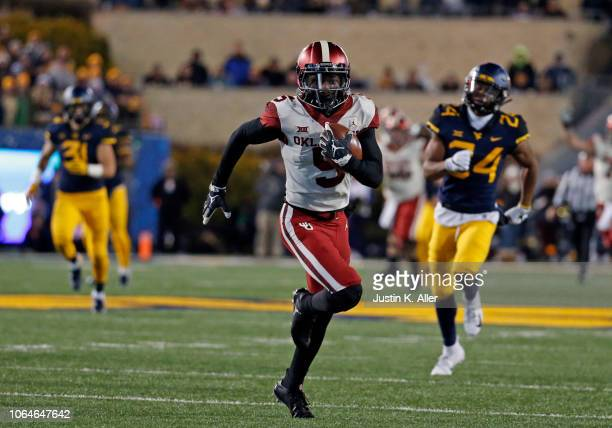Marquise Brown of the Oklahoma Sooners runs after catching a 65 yard pass against the West Virginia Mountaineers on November 23 2018 at Mountaineer...