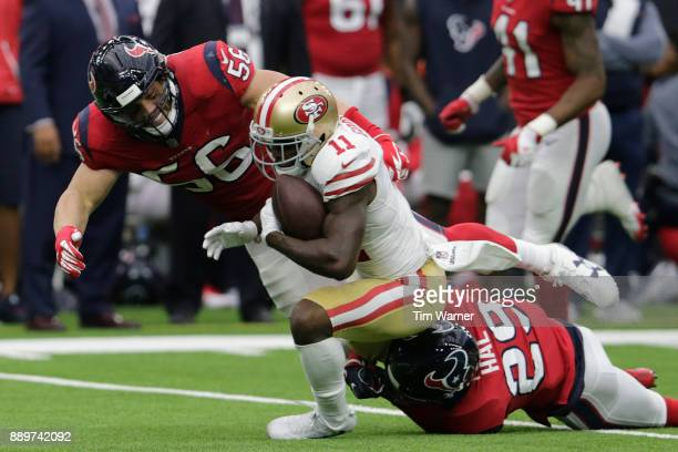 Marquise Goodwin of the San Francisco 49ers is tackled by Brian Cushing of the Houston Texans and Andre Hal in the second quarter at NRG Stadium on...