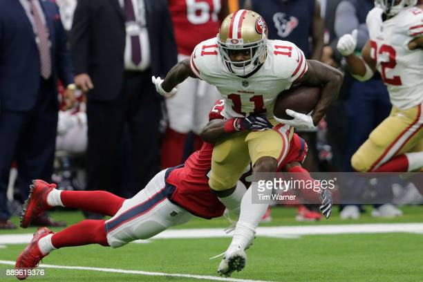 Marquise Goodwin of the San Francisco 49ers runs after catching a pass, tackled by Andre Hal of the Houston Texans at NRG Stadium on December 10,...