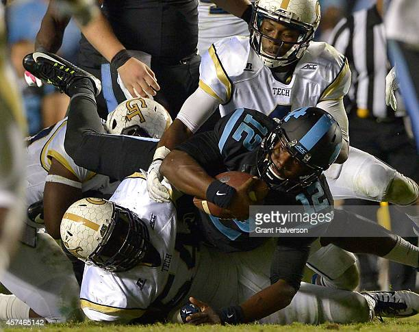 Marquise Williams of the North Carolina Tar Heels dives over Quayshawn Nealy of the Georgia Tech Yellow Jackets for extra yardage during their game...