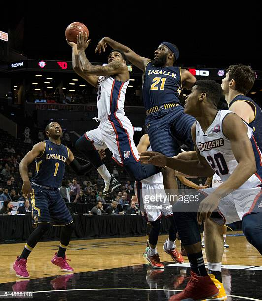 Mar'Qywell Jackson of the Duquesne Dukes attempts a shot against Jordan Price of the La Salle Explorers in the first round of the men's Atlantic 10...