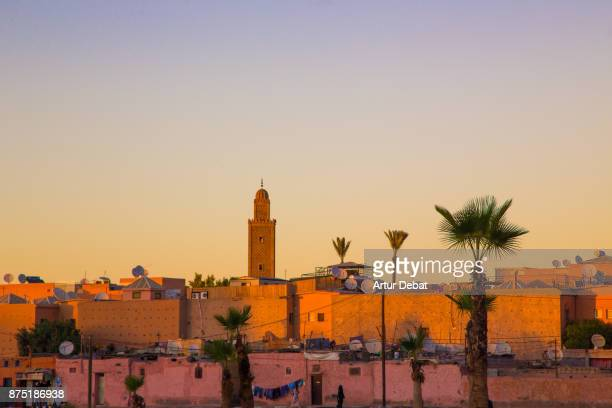 marrakech cityscape during sunset taken from building terrace with mosque silhouettes and nice colors in the sky during travel vacations in morocco. - marruecos fotografías e imágenes de stock