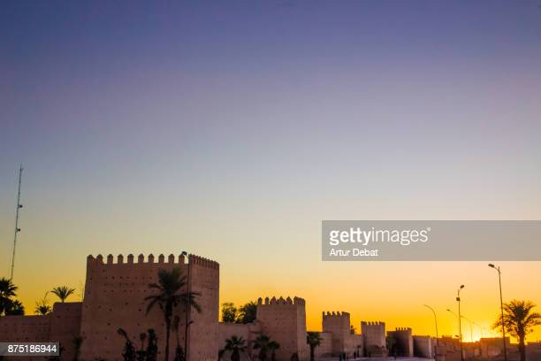 Marrakech cityscape during sunset taken from building terrace with wall and nice colors in the sky during travel vacations in Morocco.