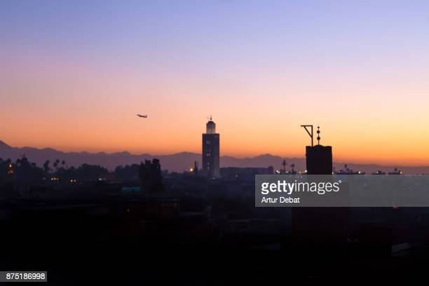 Marrakech cityscape during sunset taken from building terrace with mosque silhouettes and nice colors in the sky during travel vacations in Morocco.