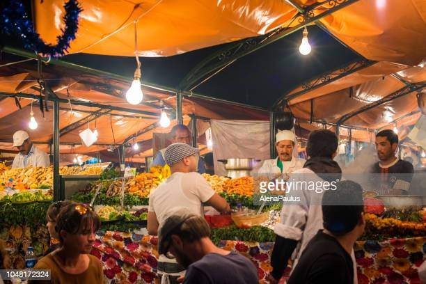 marrakech, djemma el fan square, night street market, morocco - muslim woman darkness stock photos and pictures