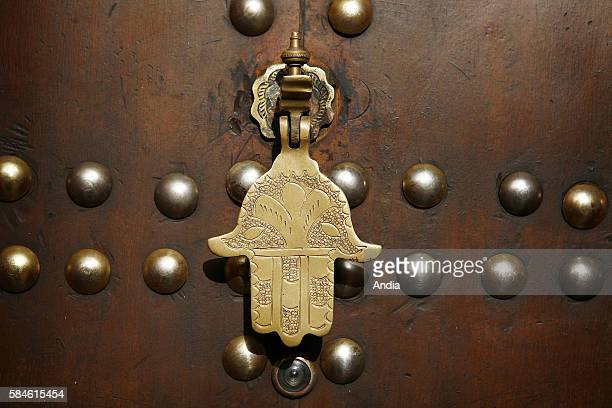 brass hand of Fatima on the frontdoor of a house