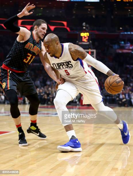 Marreese Speights of the LA Clippers dribbles past Mike Muscala of the Atlanta Hawks during the first half of a game at Staples Center on February 15...