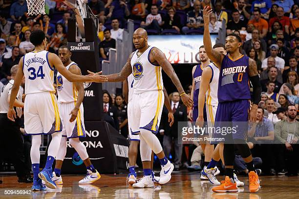 Marreese Speights of the Golden State Warriors highfives Shaun Livingston after scoring against the Phoenix Suns during the second half of the NBA...