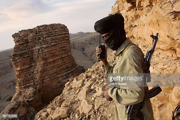 Marri tribal guerrilla speaks with a rebel observation post while directing mortar fire on a Pakistani troop outpost near Kahannear Kahan on January...