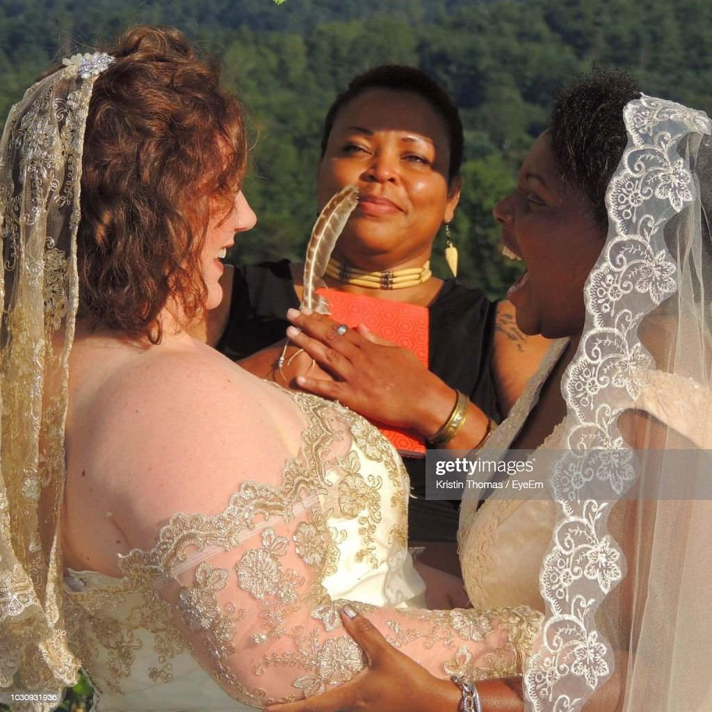 Marriage Officiant Looking At Cheerful Lesbian Couple Getting Married : Stock Photo