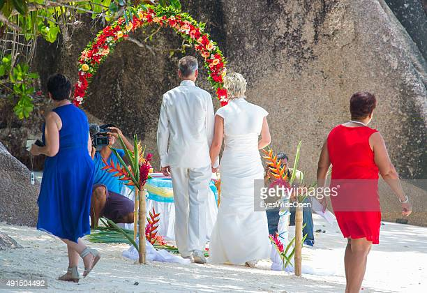 Marriage under palmtrees in white elegant clothes at the famous Source D´Argent Beach on October 01 2015 in La Passe La Digue Seychelles