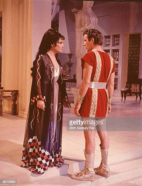 Married actors Elizabeth Taylor and Richard Burton stand in costume as Cleopatra and Marc Antony in a still from the film 'Cleopatra' directed by...