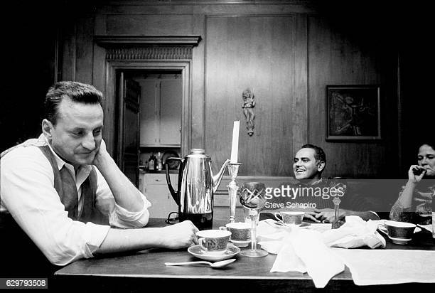 Married actors George C Scott and Colleen Dewhurst with an unidentified man sit at a table in their home New York 1963