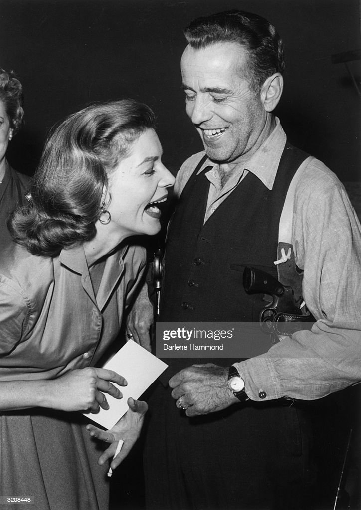 Married actors Lauren Bacall and Humphrey Bogart laughing on set between takes of the Producer's Showcase live telecast of 'The Petrified Forest', in which they both star. Bacall holds a cigarette and Bogart wears two guns.