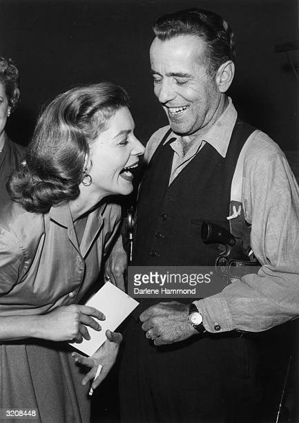 Married actors Lauren Bacall and Humphrey Bogart laughing on set between takes of the Producer's Showcase live telecast of 'The Petrified Forest', in...