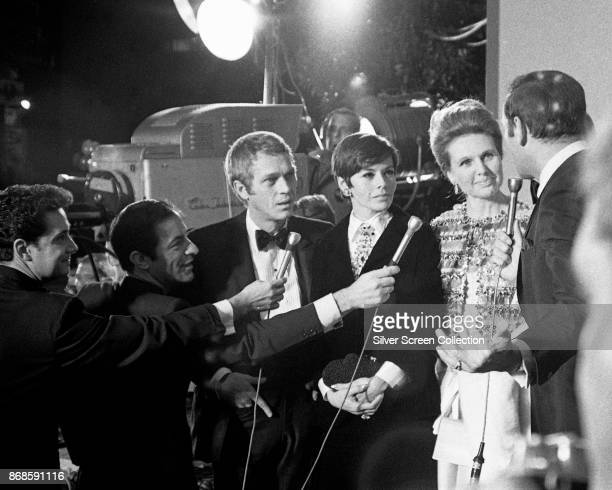 Married actors Steve McQueen and Neile Adams listen as several reporters interview actress Sheila Sim at the premiere of the 'Doctor Dolittle' at the...