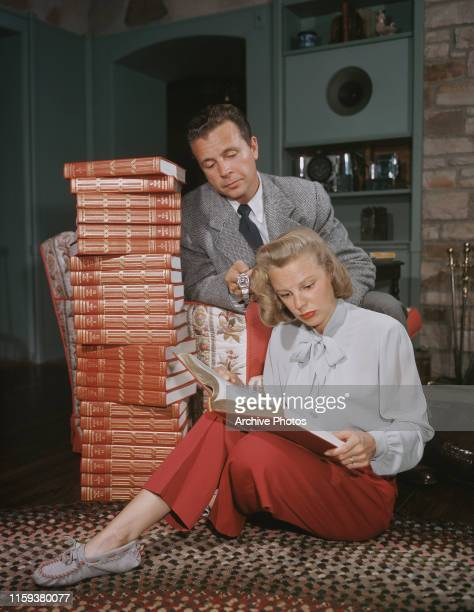 Married American actors Dick Powell and June Allyson reading a new set of the 'Encyclopaedia Britannica' USA circa 1947