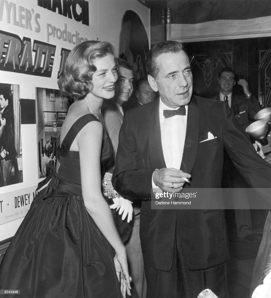 Married American actors Humphrey Bogart (1899 - 1957) and Lauren Bacall attend the premiere of director William Wyler's film, 'The Desperate Hours' in which Bogart starred. Bogart is holding a cigarette.