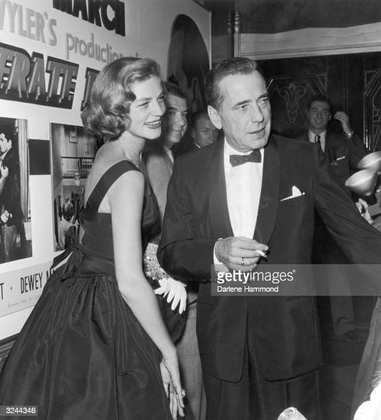 Married American actors Humphrey Bogart and Lauren Bacall attend the premiere of director William Wyler's film 'The Desperate Hours' in which Bogart...