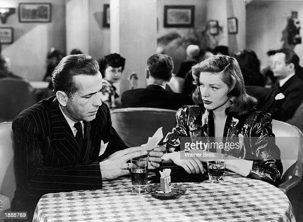 Married American actors Humphrey Bogart and Lauren Bacall sit together at a bar in a still from the film, 'The Big Sleep,' directed by Howard Hawks,...