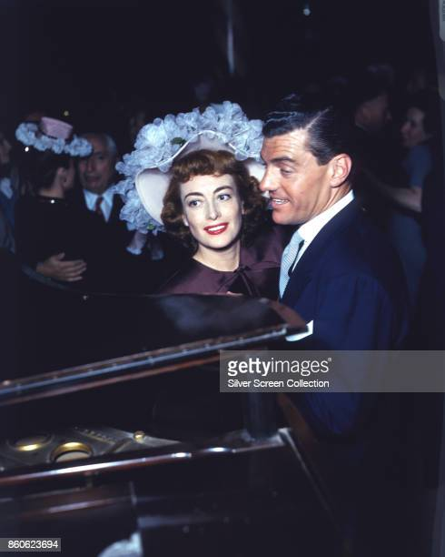 Married American actors Joan Crawford and Phillip Terry dance beside a piano at an uspecified event mid to late 1940s