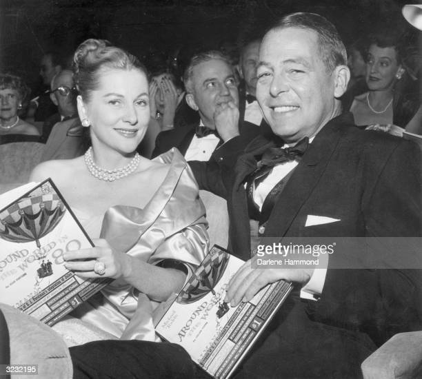 Married American actors Joan Fontaine and Collier Young smile as they sit in the audience for the premiere of director Michael Anderson's film...