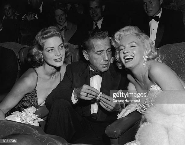 Married American actors Lauren Bacall and Humphrey Bogart pose with American actor Marilyn Monroe at the premiere of director Jean Negulesco's film...