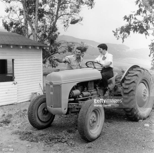 Married American actors Ronald Reagan and Nancy Davis preparing for a day's work on their ranch Malibu California Davis is seated in the driver's...