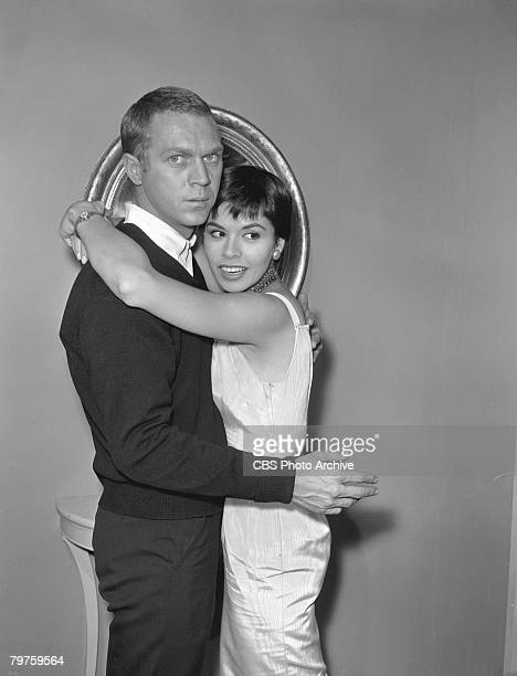 Married American actors Steve McQueen and Neile Adams embrace during the filming of an episode of the television anthology series 'Alfred Hitchcock...