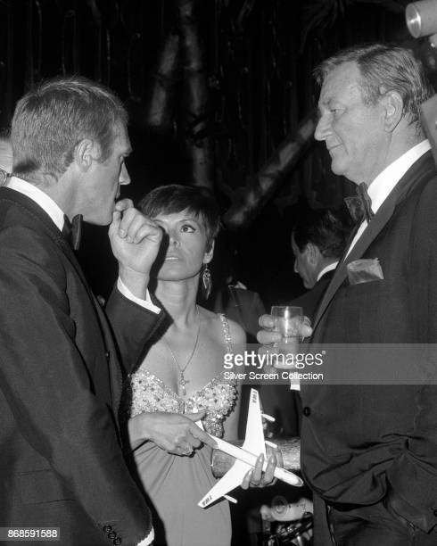 Married American actors Steve McQueen and Neile Adams talk with fellow actor John Wayne at 24th Annual Golden Globe Awards ceremony at the Cocoanut...