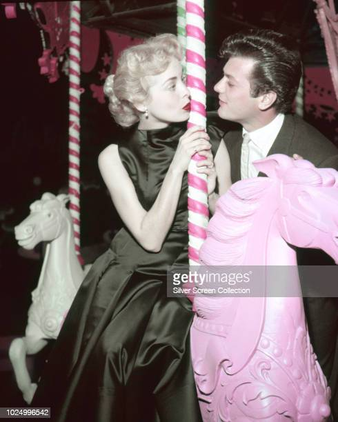 Married American actors Tony Curtis and Janet Leigh on a carousel circa 1955