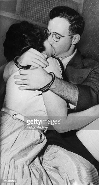 Married American traitors Julius and Ethel Rosenberg wearing handcuffs kiss in the back of a prison van after their treason arraignment New York City