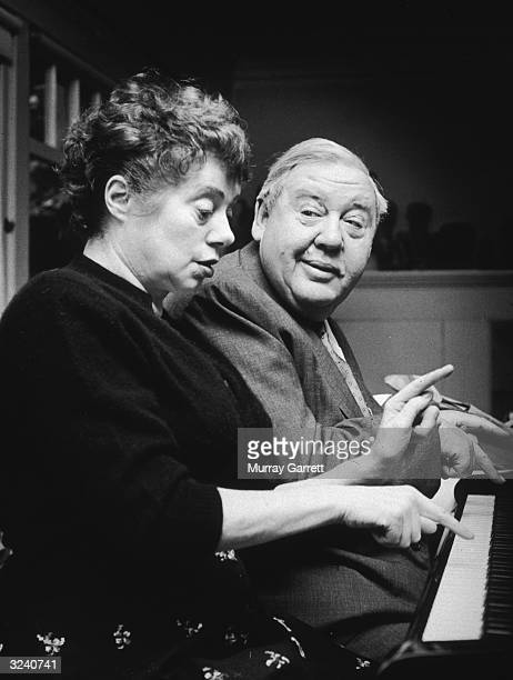 Married British actors Elsa Lanchester and Charles Laughton playing a piano duet with their index fingers at their home in Los Angeles California