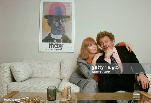 Married comedic actors Anne Meara and Jerry Stiller posing on a living room sofa.