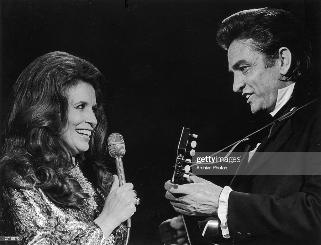 Married country singers Johnny Cash (1932 - 2003) and June Carter Cash (1929 - 2003) perform a duet on stage.